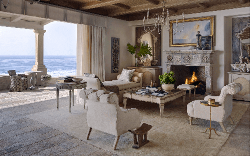An extraordinary living room with a beautiful view ocean view while having a Stone Reclaimed Fireplace with fire adding beauty to the room